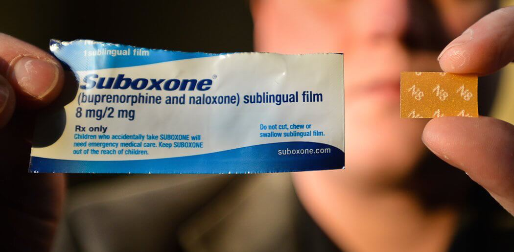 man holding suboxone package and drug