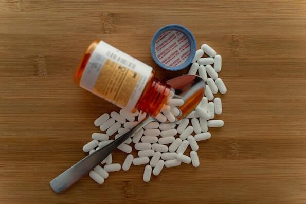 Open prescription opioid pill bottle and spoon