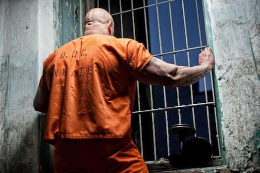 Inmate in orange jumpsuit looking out prison bar window